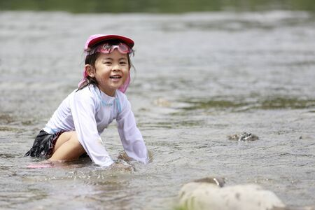 Japanese girl playing in the river (4 years old) Stock Photo