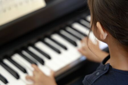 Japanese girl playing a piano (4 years old) 写真素材