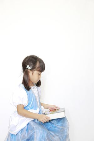 Japanese girl reading a book in a dress (4 years old)