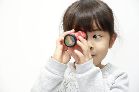 Japanese girl playing with kaleidoscope (white back) (5 years old)