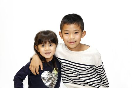 Japanese brother and sister putting arms around each other's sholders (10 years old boy and 5 years old girl) 스톡 콘텐츠