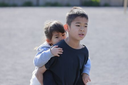 Japanese boy carrying his sister in his back (10 years old boy and 5 years old girl)
