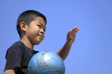 Japanese boy holding soccer ball under the blue sky (fifth grade at elementary school)