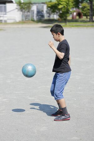 Japanese boy playing football juggling (fifth grade at elementary school)
