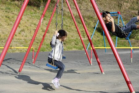 Japanese brother and sister on the swing  (10 years old boy and 5 years old girl)