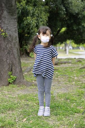 Japanese girl with a mask in the green (5 years old)