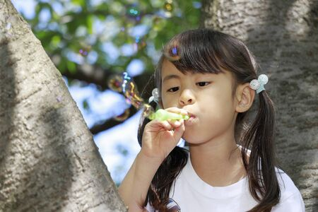 Japanese girl playing with bubble on the tree (5 years old) Stok Fotoğraf