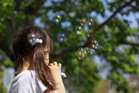 Japanese girl playing with bubble in the green (appearance from behind) (5 years old)