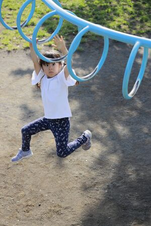 Japanese girl playing with a monkey bars (5 years old)