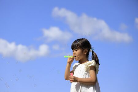 Japanese girl playing with bubble under the blue sky (5 years old)
