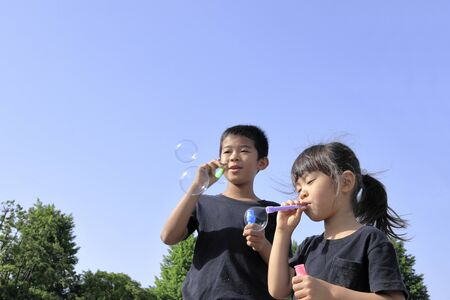 Japanese brother and sister playing with bubble under the blue sky (10 years old boy and 5 years old girl)