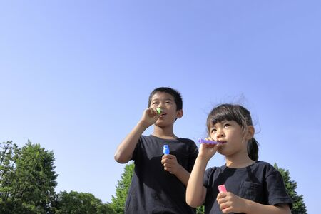 Japanese brother and sister playing with bubble under the blue sky (10 years old boy and 5 years old girl) 스톡 콘텐츠
