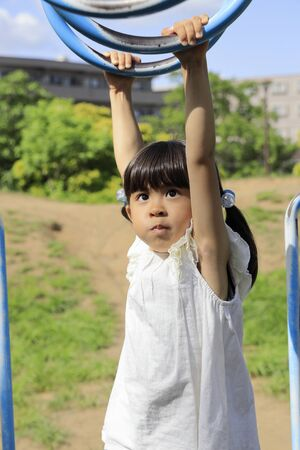 Japanese girl playing with a monkey bars (5 years old) Stok Fotoğraf