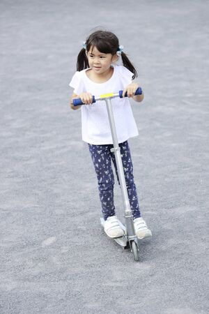 Japanese girl riding on a scooter (5 years old) Stok Fotoğraf