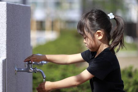 Japanese girl washing her hands at the park (5 years old)