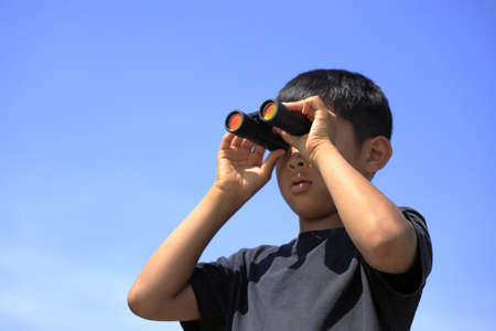 Japanese boy with opera glass under the blue sky (10 years old)