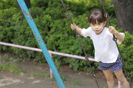 Japanese girl standing on the swing (5 years old)