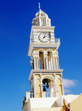 a picture taken in Santorini depicting a bright yellow church tower