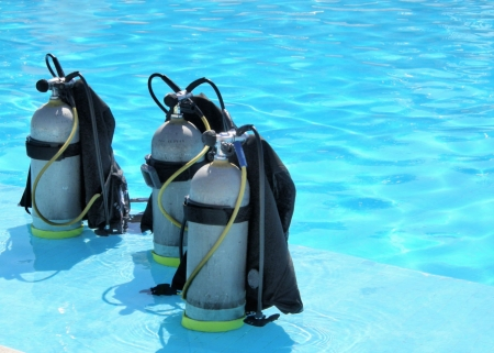travel gear: a picture of three oxygen tanks lying on the shallow part of a pool
