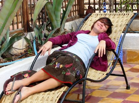 an attractive woman is lying on a lounge chair on a terrasse Reklamní fotografie