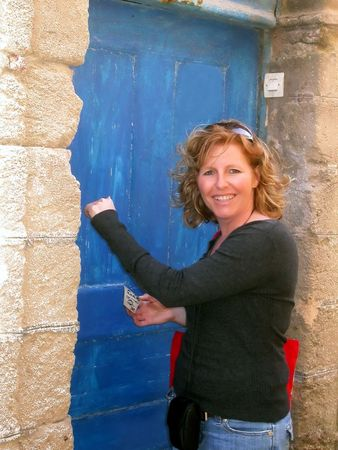 knock on door: a woman in her thirties is knocking on an old wooden blue door Stock Photo