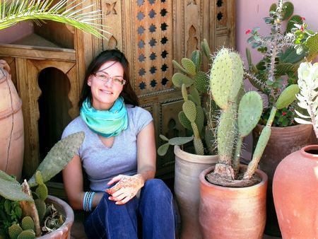 a young woman tourist is sitting amidst cactuses and showing a henna tatoo