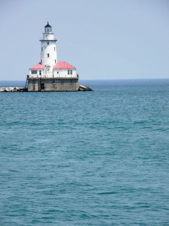 lighthouse at the end of a pier on a lake photo