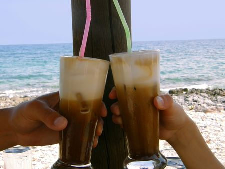 female and male hands sharing iced coffee by the sea