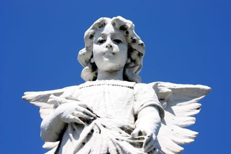 white angel tombstone on blue sky background