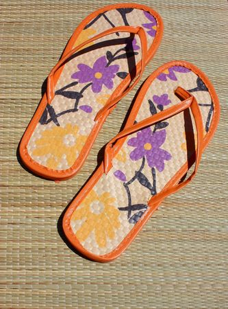 pair of tong sandals on beach mat photo
