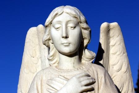 guardian angel statue against blue sky
