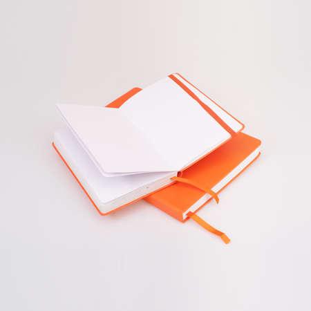 Two orange notebooks isolated on a white background