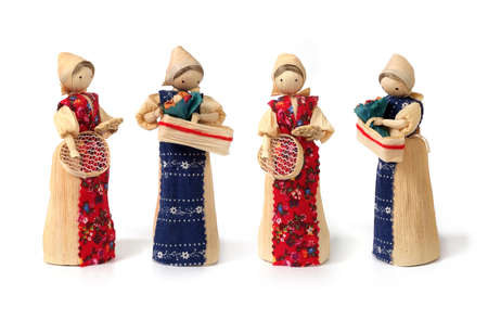 Set of straw souvenir dolls in national costumes isolated on white background