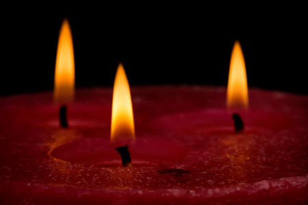 A large candle on a ceramic plate isolated on black background