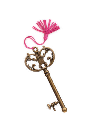 Old golden key with pink tassel isolated on white background