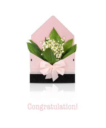 Pink box with silk bow and bouquet of lilies of the valley for gifts isolated on white background