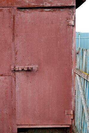 old red metal garage door with a sation. Banco de Imagens