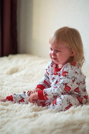 Little girl sitting on the bed crying