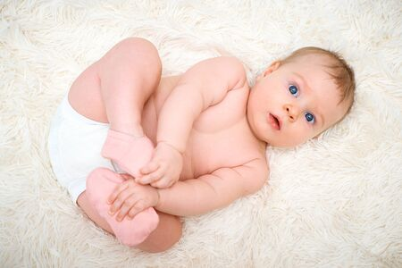 a small child is lying on his back and holding on to the legs