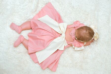 A little girl in a pink dress with a bow is lying on a white wool blanket. The view from the top.