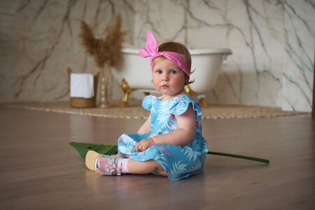 A small beautiful girl is sitting on the floor in a blue dress