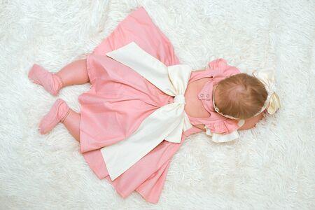 A little girl in a beautiful dress is lying on a blanket