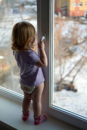 A little girl standing in front of a window. High quality photo