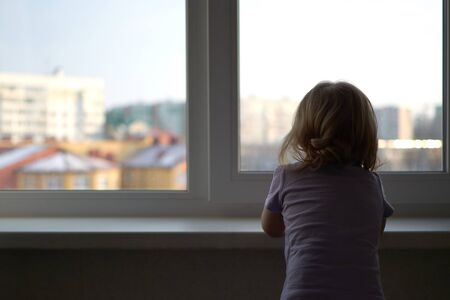 A little girl standing in front of a window Banco de Imagens