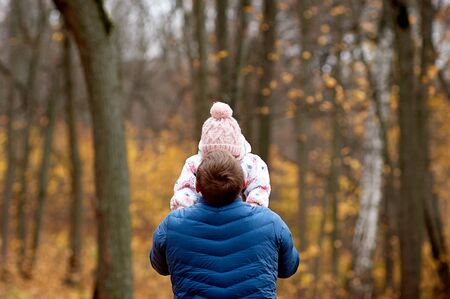 Dad stands with his back and holds his daughter in his arms in the autumn forest.