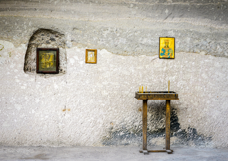gray wall with icons, small table with church candles