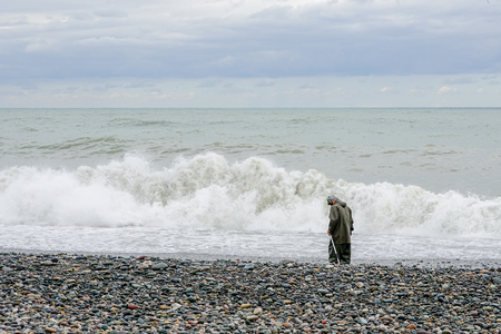 A man with a metal detector walks along the beach of the Black Sea, treasure hunter Foto de archivo