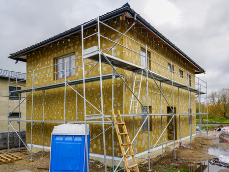 Modern single family two store home under construction, enclosed with scaffolds, thermal insulation Stock Photo - 114279782