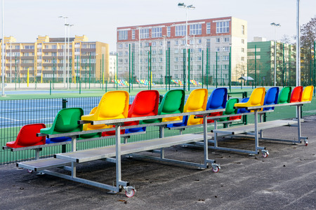 portable small size metal stands with colorful plastic seats for spectators in the stadium