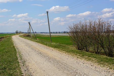 gravel rural road along a green field against a blue sky with white clouds